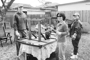 two woman and man painting table