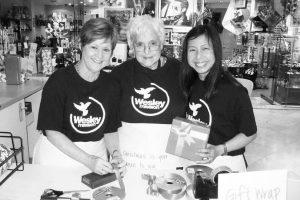 Three Wesley Mission volunteer women wearing logo on tops
