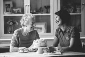 volunteer and older client smiling having morning tea in kitchen