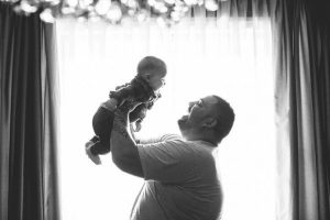 father holding baby in the air smiling