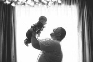 father lifting baby in the air smiling
